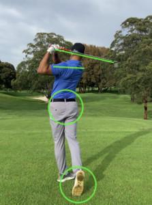 Golfer in blue shirt showing proper follow through